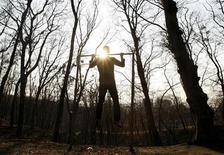 A man does chin-ups at a city park in Kiev, March 19, 2012. REUTERS/Anatolii Stepanov