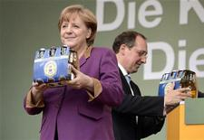 German Chancellor Angela Merkel smiles after she received a pack of famous Flensburger beer during an election rally with Schleswig-Holstein's Christian Democratic (CDU) chairman and top candidate Jost de Jager (R) in Flensburg, April 26, 2012. REUTERS/Fabian Bimmer