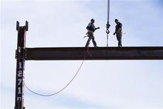 Ironworkers Jim Brady (R) and Billy Geoghan walk onto an iron beam after maneuvering it into place on the 100th story of One World Trade Center in New York, April 30, 2012. REUTERS/Lucas Jackson