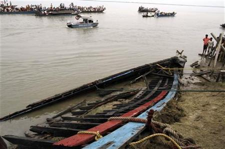 Onlookers and rescue workers look at the damaged boat which was taken on shore after it sank on the Brahmaputra river, at Buraburi village in Dhubri district of Assam May 1, 2012. REUTERS/Utpal Baruah
