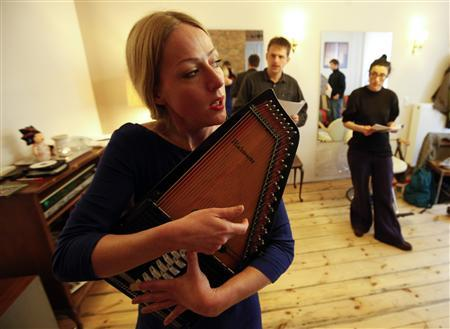 German singer Doreen Kutzke (L) plays a stringed instrument during she conducts a yodel workshop watched by participants at Berlin's Kreuzberg district March 31, 2012. REUTERS/Fabrizio Bensch