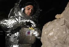 Physicist Daniel Schildhammer takes a rock sample as he wears the Aouda.X spacesuit simulator during a field test of Oesterreichisches Weltraum Forum (Austrian space forum) inside the Eisriesenhoehle (giant ice cave) at Dachstein mountain near the village of Obertraun April 28, 2012. REUTERS/Lisi Niesner