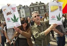 """A man and a woman hold signs which read, """"19357 deaths caused by tobacco, zero by cannabis"""" and """"3855 deaths caused by liquor and zero by cannabis"""" (R) during a protest march against a ban on selling cannabis to foreigners, in front of the town hall in Maastricht May 1, 2012. Tourists puffed on spliffs in the streets of southern Dutch cities and defiant coffee-shops sold joints to visitors in protest against the ban which took effect on Tuesday. REUTERS/Michael Kooren"""