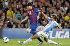 Lionel Messi disputa lance com Ignacio Camacho, do Málaga, duranta partida em que o argentino marcou 3 vezes para o Barcelona e bateu recorde de gols numa temporada. REUTERS/Albert Gea