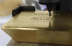 Машина гравирует слиток золота на фабрике в Красноярске, 28 марта 2011 года. Золотовалютные резервы России на 27 апреля составили $523,3 миллиарда - максимальное значение с конца сентября 2011 года. REUTERS/Ilya Naymushin