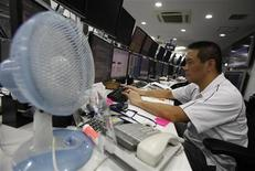 Трейдер следит за торгами в зале биржи в Токио, 26 июля 2011 года. Азиатские фондовые рынки, кроме Китая, снизились в четверг из-за слабых показателей занятости в США. REUTERS/Yuriko Nakao