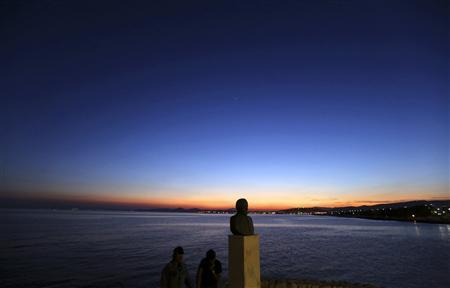 Two men enjoy a warm evening by the coast near Athens May 2, 2012. REUTERS/Yannis Behrakis