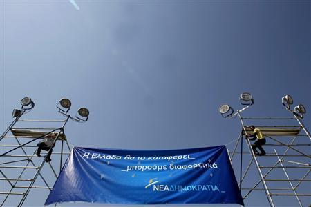 Workers place a banner for a pre-election campaign rally of the New Democracy party in Athens May 3, 2012. Greece holds general elections on May 6. REUTERS/Yorgos Karahalis