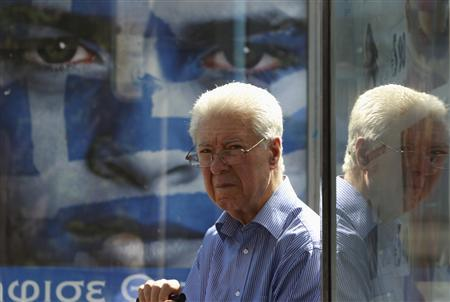 A man sits in a bus station with an election campaign poster in Athens May 3, 2012. Greece will call a snap election for May 6. REUTERS/John Kolesidis