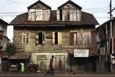 A pedestrian walks past a traditional colonial-era Board House dating back about a century on Pademba Road in Sierra Leone's capital Freetown April 27, 2012. Scattered across Sierra Leone's capital Freetown stand ageing wooden houses, some of which look more like they belong on the east coast of 18th century America than in a steamy west African city. Others look like they may have been built hundreds of years ago in the islands of the Caribbean, another reflection of Sierra Leone's history as a colony established for freed slaves. REUTERS/Finbarr O'Reilly