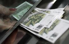 Кассир принимает грузинские лари в офисе банка в Тбилиси 1 февраля 2010. Ведущая страховая компания Грузии Aldagi BCI купила третью по величине, продолжив консолидацию в секторе, на рост доходности которого рассчитывает крупнейший частный банк страны, чьи акции обращаются на Лондонской бирже. REUTERS/David Mdzinarishvili