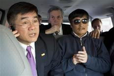 A handout photo from the U.S. Embassy Beijing Press office shows U.S. Ambassador to China Gary Locke (L) talking on a mobile phone as he accompanies blind activist Chen Guangcheng (R) in a car, in Beijing, May 2, 2012. Picture taken May 2, 2012. REUTERS/US Embassy Beijing Press Office/Handout