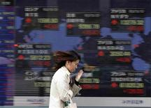 A woman walks past an electronic stock board outside a brokerage in Tokyo May 2, 2012. Asian shares rose and the dollar recovered against the yen on Wednesday after strong U.S. factory activity data raised hopes that the world's biggest economy remained on a recovery track while growth in Asian manufacturing improved broader sentiment. REUTERS/Kim Kyung-Hoon