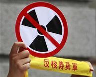 Демонстрант держит плакат с перечеркнутым символом атомной энергии во время акции у президентского дворца в Тайбэе 25 апреля 2011 года. Электроэнергетическая компания Hokkaido Electric Power Co начала в субботу отключение последней действующей в Японии атомной электростанции, в результате чего страна останется без атомной энергии впервые с 1970 года. REUTERS/Nicky Loh