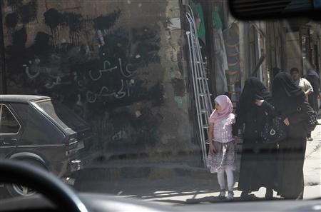 Local residents walk near anti-Assad graffiti that have been painted over, during a field visit by U.N. observers in Douma city, near Damascus May 5, 2012, one of the locations where there are protests against the regime of Syrian President Bashar al-Assad. REUTERS/Khaled al-Hariri