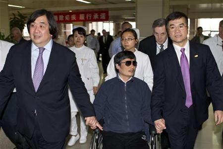 A handout photo from the U.S. Embassy Beijing Press office shows blind activist Chen Guangcheng (C) sitting in a wheelchair as he is accompanied by U.S. Ambassador to China Gary Locke (R) at a hospital in Beijing, May 2, 2012. REUTERS/US Embassy Beijing Press Office/Handout