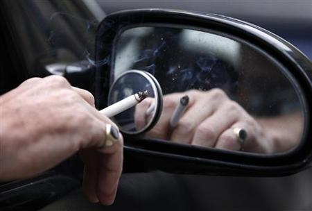 A man smokes a cigarette as he sits in his car in Liverpool, northern England November 16, 2011. REUTERS/Phil Noble/Files