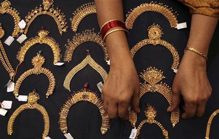 A woman checks a gold necklace inside a jewellery showroom in Hyderabad April 11, 2012. REUTERS/Krishnendu Halder