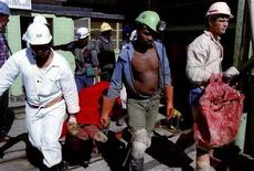 Miners involved in rescue operations carry the body of a colleague killed in an underground accident at a South African mine in a file photo. REUTERS/old