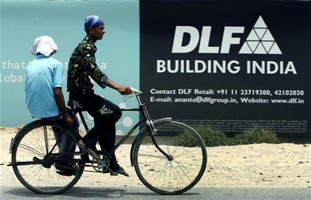 A man rides pass an advertisement of Indian property developer DLF Ltd. in Gurgaon June 11, 2007. REUTERS/Adnan Abidi/Files