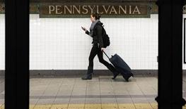 A woman wheels luggage along the subway platform at the 34th Street Penn Station stop in New York November 23, 2011. REUTERS/Shannon Stapleton