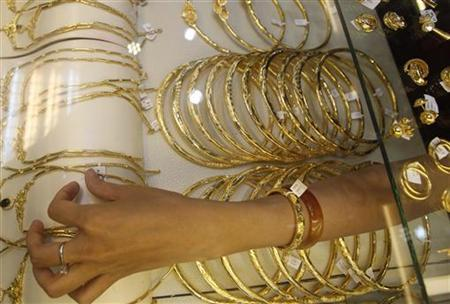 A woman displays gold for sale at a gold shop in Hanoi August 9, 2011. REUTERS/Kham/Files