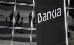 Люди отражаются в зеркалах на здании офиса банка Bankia в Мадриде, 9 мая 2012 года. Испания взяла под контроль Bankia, четвертый крупнейший банк страны, пытаясь развеять опасения по поводу способности правительства навести порядок в финансовом секторе. REUTERS/Paul Hanna