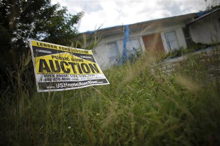 An auction sign for a property is seen at the front garden of a foreclosed house in Miami Gardens, Florida September 15, 2009. REUTERS/Carlos Barria