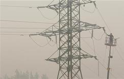 Электрик ремонтирует линию электропередачи, поврежденную лесными пожарами, в селе Криуша Рязанской области, 7 августа 2010 года. Российские власти планируют передать государственный распредсетевой Холдинг МРСК в управление другой сетевой монополии ФСК, сказали Рейтер источники, знакомые с ситуацией, и подтвердил представитель министерства энергетики. REUTERS/Denis Sinyakov