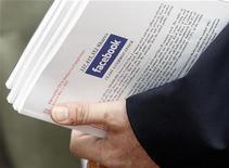 Инвестор держит проспект по первичному размещению Facebook во время роуд-шоу в Бостоне, 8 мая 2012 года. Спрос на акции Facebook Inc, готовящейся к рекордному первичному размещению, превысил предложение уже через несколько дней после того, как крупнейшая в мире социальная сеть запустила роуд-шоу, сообщил источник, знакомый с листингом. REUTERS/Jessica Rinaldi