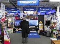 Мужчина смотрит телевизоры Panasonic в магазине в Токио, 3 февраля 2012 года. Чистый убыток Panasonic Corp за 12 месяцев к концу марта 2012 года составил рекордные 772,2 миллиарда иен ($9,7 миллиарда), однако компания намерена в новом финансовом году повысить прибыльность за счет сокращения издержек и увольнений. REUTERS/Kim Kyung-Hoon