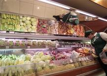 Работница супермаркета в Москве складывает овощи в пакет, 3 июня 2011 года. Инфляция в РФ за неделю с 29 апреля по 5 мая составила 0,1 процента, с начала месяца потребительские цены выросли на 0,1 процента, с начала года - на 1,8 процента, сообщил Росстат. REUTERS/Alexander Natruskin