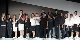 Italian designer Giorgio Armani acknowledges applause with Italian athletes who will participate in the London 2012 Olympic Games during the presentation of the Italy's official Olympic kit in Milan, May 10, 2012. REUTERS/ Stefano Rellandini