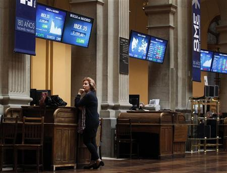 A woman stands under session information screens at the Madrid bourse April 27, 2012. REUTERS/Andrea Comas