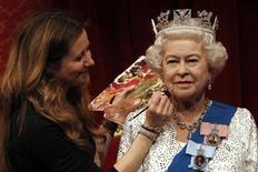 Funcionária do Madame Tussauds Lisa Burton posa com o novo modelo da Rainha Elizabeth, produzida em homenagem ao Jubileu de Diamante, em Londres. 14/05/2012 REUTERS/Suzanne Plunkett