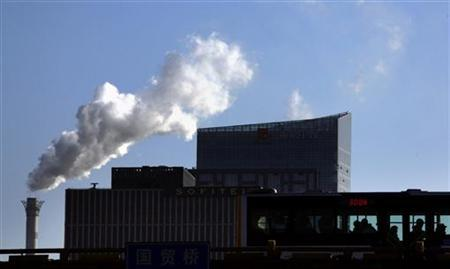 Passengers on a bus can be seen in front of a chimney for a coal-burning heating system as it billows smoke in central Beijing December 12, 2011. REUTERS/David Gray/Files