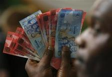 A man holds Ghana's cedi notes in a file photo. REUTERS/Luc Gnago