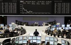Traders work at their desks in front of the DAX board at the Frankfurt stock exchange May 14, 2012. REUTERS/Remote/Kirill Iordansky