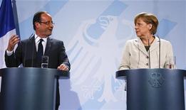 Президент Франции Франсуа Олланд (слева) и канцлер Германии Ангела Меркель выступают на пресс-конференции в Берлине, 15 мая 2012 года. Новый президент Франции Франсуа Олланд и канцлер Германии Ангела Меркель признали во вторник различия в подходе к побуждению роста в скатившейся в рецессию Европе, но пообещали разработать общую стратегию перед саммитом Евросоюза в следующем месяце. REUTERS/Fabrizio Bensch