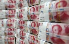 Пачки китайских юаней в отделении банка в Сеуле, 8 октября 2010 года. Банковские регуляторы Китая изучают случаи неравномерности темпов предоставления новых кредитов, но не планируют менять соотношение кредитов к депозитам, которого должны придерживаться банки, сообщил вице-председатель надзорного органа в среду. REUTERS/Lee Jae-Won