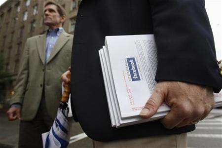 An investor holds literature explaining the Facebook stock after attending a show for Facebook Inc's initial public offering at the Four Season's Hotel in Boston, Massachusetts May 8, 2012. REUTERS/Jessica Rinaldi