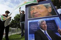 Protestors hold signs and pictures of CEO Jamie Dimon as JP Morgan Chase & Co convenes its annual shareholders meeting at the bank's back-office complex in Tampa, Florida, May 15, 2012. REUTERS/Brian Blanco