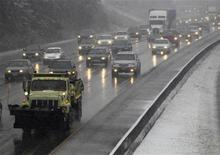 A snowplow leads the traffic on the I-5 Interstate Highway as snow falls in Seattle January 17, 2012. REUTERS/Anthony Bolante