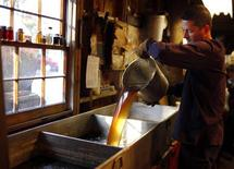 Steve Randle, a software engineer during the work-week, pours freshly made maple syrup in the finishing pan at Hollis Hills Farm in Lunenburg, Massachusetts February 19, 2012. REUTERS/Brian Snyder