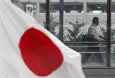 Бизнесмен проходит около развивающегося флага Японии в Токио, 24 августа 2011 года. Экономика Японии восстановилась в первом квартале после прошлогоднего спада благодаря реконструкции разрушенного землетрясением и цунами северо-востока, высоким расходам потребителей и улучшению экспорта. REUTERS/Issei Kato