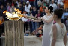 A atriz grega Ino Menegaki acende a tocha a partir da pira com a chama olímpica durante cerimônia de entrega à Grã-Bretanha, em Atenas, na Grécia, nesta quinta-feira. 17/05/2012 REUTERS/John Kolesidis