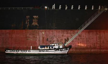 Indian police personnel walk down from the Napoli-registered Italian merchant vessel Enrica Lexie, which is anchored at outer sea, as the ship prepares to sail out from Kochi May 5, 2012. REUTERS/Sivaram V