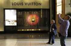 Tourists are pictured in front of a Louis Vuitton boutique in Hollywood, California March 20, 2012. REUTERS/Fred Prouser