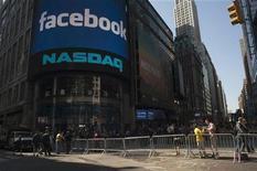 Пешеходы проходят мимо NASDAQ в Нью-Йорке 18 мая 2012 года. Бумаги социальной сети Facebook Inc начали торги ростом на 13 процентов, после того как компании удалось привлечь на одном из крупнейших IPO в истории США внушительные $18,4 миллиарда. REUTERS/Keith Bedford