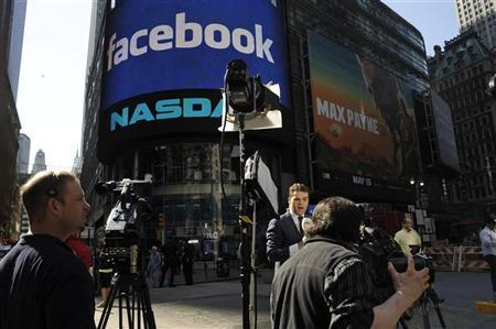 Members of the media deliver their reports in front of the NASDAQ Marketsite at the start of the listing for Facebook in New York, May 18, 2012. REUTERS/Keith Bedford